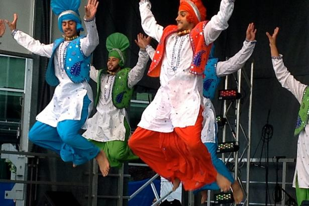 Male performers mid-jump on-stage at Celebrate the Harvest