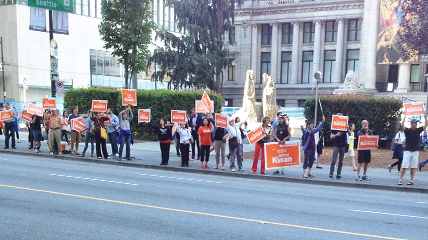 NDP supporters wave signs at a morning rush-hour rally downtown