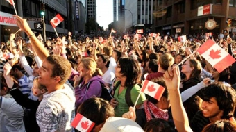 Crowds wave the red-and-white at a Canada Day parade in downtown Vancouver.